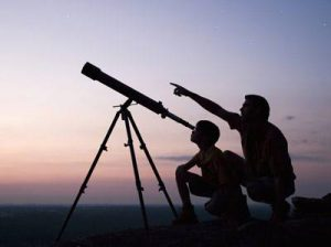 Photo of two people looking through a telescope silhouetted against a darkening sky